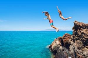 kinderen springen van de rotsen in de helderblauwe zee op Ibiza