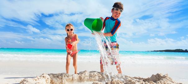 Kinderen aan het spelen op het strand met een zandkasteel.