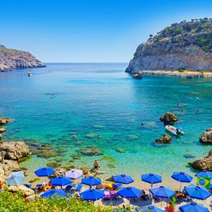 Het strand van Anthony Queen Bay met blauwe parasols en kristalhelder water