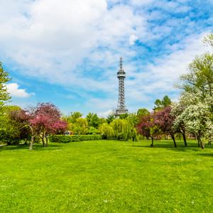 Park met grasveld en bomen met op de achtergrond de Petřín toren