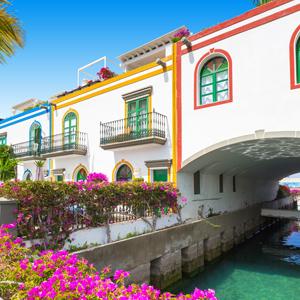 Pastelkleurige huizen met roze bloesem aan de kanaaltjes en haven van Puerto de Mogán