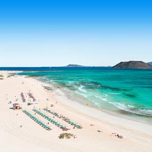 Witte zandstrand met ligbedjes bij ruige zee op het eiland Fuerteventura