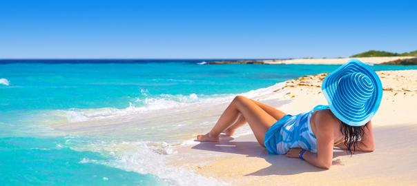 Vrouw met hoed op een strand